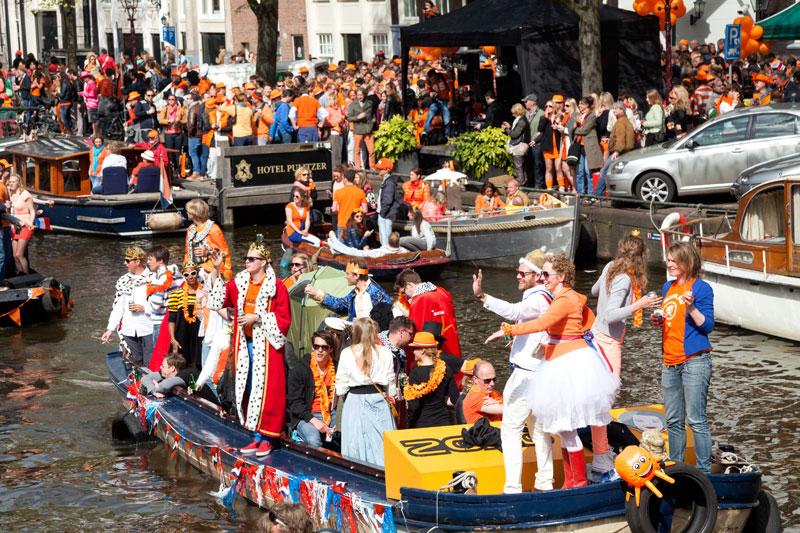 Drukte in de grachten van Amsterdam tijdens koningsdag. Koningsdag, koninginnedag, vieren, typisch Hollands, Nederland, vieren, feest, festival, Amsterdam, oranje,