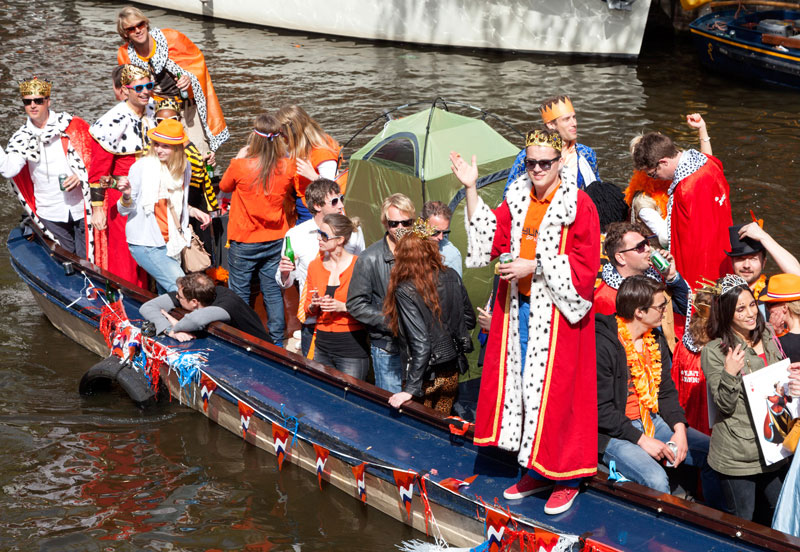 De 'koning' en zijn sloep in Amsterdam. Koningsdag, koninginnedag, vieren, typisch Hollands, Nederland, vieren, feest, festival, Amsterdam, oranje,