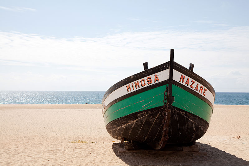A fishing boat on the sandy beach of Nazare, Portugal