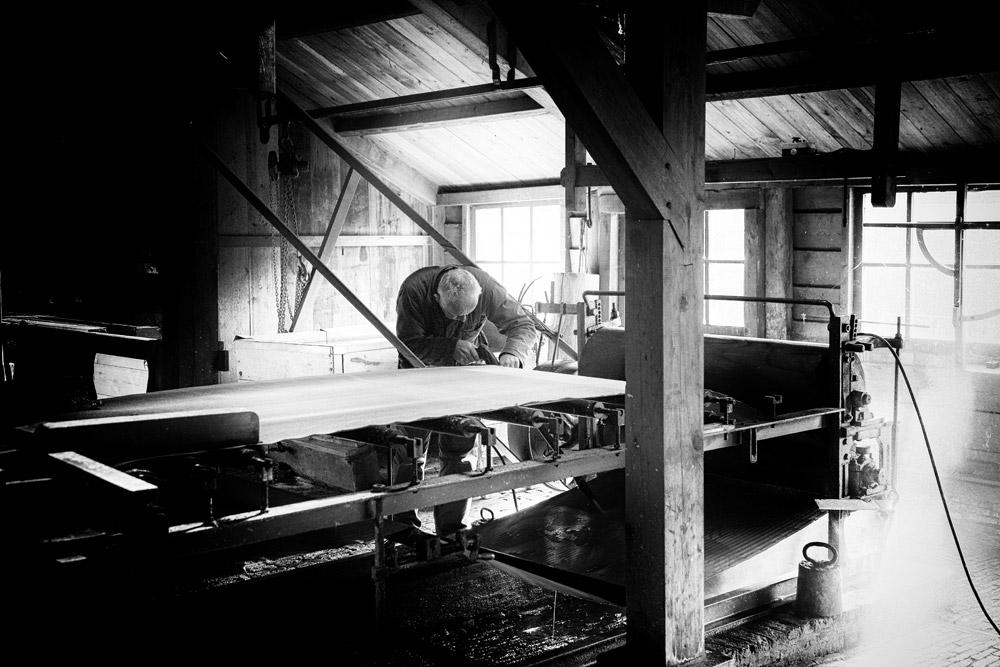 De molenaar maakt de papiermachine schoon van papiermolen De Schoolmeester, Westzaan, Nationale Molendag